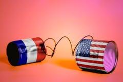 有美国和法国旗子的锡罐电话 黑色通信概念收货人电话 库存图片