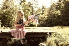 有美国国旗的愉快的小女孩独立日 免版税图库摄影