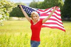 有美国国旗的美丽的爱国的少妇 库存照片