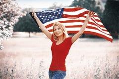 有美国国旗的美丽的爱国的少妇 免版税库存照片