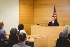 有美国国旗的面无笑容的法官在他后 免版税库存照片