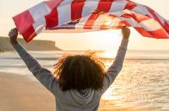 有美国旗子的混合的族种非裔美国人的女孩少年在海滩 图库摄影