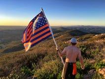 有美国橄榄球联盟丹佛野马旗子的远足者在山山顶 免版税库存照片