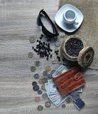 有美国美元、各种各样的外国硬币、太阳镜和咖啡的红色钱包在桌上的 免版税库存照片