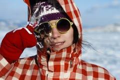 有美好的光芒四射的微笑的一个女孩在晴朗的黄色玻璃和红色手套拿着从贝加尔湖的冰柱 免版税库存图片