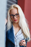 有美好的出现和长的头发的年轻美丽的微笑的白肤金发的女孩 玻璃和迷人的神色的微笑的女孩 免版税库存照片