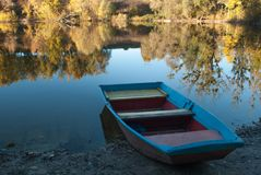 有美好的反射的湖和在岸的一条小船 图库摄影