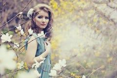有美好的发型的美丽的金发碧眼的女人在一株豪华的春天庭院木兰的葡萄酒蓝色礼服 免版税库存图片