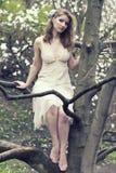 有美好的发型的美丽的金发碧眼的女人在一株豪华的春天庭院木兰的葡萄酒蓝色礼服 库存图片