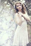 有美好的发型的美丽的金发碧眼的女人在一株豪华的春天庭院木兰的葡萄酒蓝色礼服 库存照片