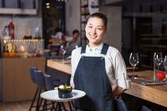有美好的微笑的女孩侍者在她的手上拿着意大利烹调命令甜点心盘  穿戴在有壳 免版税库存照片