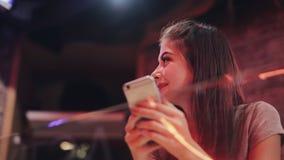 有美好的微笑的年轻可爱的妇女在晚上使用智能手机 坐在酒吧或餐馆的性感的女孩 股票视频