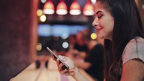 有美好的微笑的年轻可爱的妇女在晚上使用智能手机 坐在酒吧或餐馆的性感的女孩 影视素材