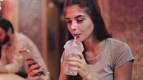 有美好的微笑的年轻可爱的妇女在晚上使用智能手机 坐在酒吧或餐馆的性感的女孩 股票录像