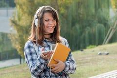 有美好的微笑的愉快的校园女孩 库存图片