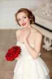 有美好的微笑的迷人的白肤金发的女孩在一件白色鞋带礼服 库存图片