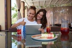 有美好的微笑的年轻迷人的妇女有在触摸板的电视电话会议,当坐在咖啡店时 图库摄影