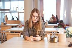 有美好的微笑读的好消息的迷人的妇女在休息期间的手机在咖啡馆 图库摄影