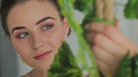 有美好的构成和发型的妇女在用花装饰的摇摆 股票录像