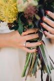 有美好的红色修指甲和豪华圆环的新娘手与金刚石拿着婚礼花束 特写镜头 免版税库存照片
