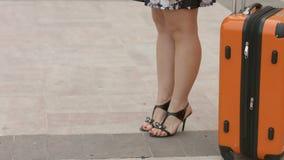 有美好的腿的妇女在等待火车,在驻地的公共汽车的高跟鞋鞋子 影视素材