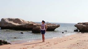 有美好的腿的少妇走开沿干净的金黄沙滩的 股票录像