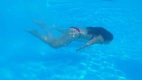 有美好的身体跃迁和游泳的匀称腿长的女朋友水下在清楚的蓝色水池在夏天休假期间在 股票录像