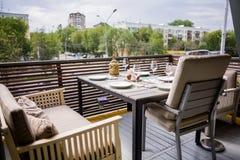 有美妙地用装备的内部、舒适的扶手椅子和服务的桌的一家餐馆在一个宽敞室外大阳台 图库摄影