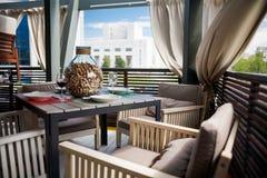 有美妙地用装备的内部、舒适的扶手椅子和服务的桌的一家餐馆在一个宽敞室外大阳台 免版税库存图片