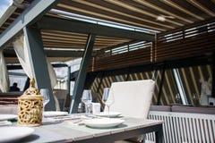 有美妙地用装备的内部、舒适的扶手椅子和服务的桌的一家餐馆在一个宽敞室外大阳台 免版税库存照片