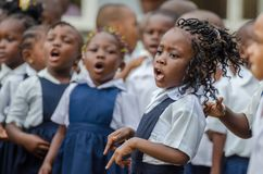 有美妙地装饰的头发的年轻非洲学校女孩唱歌和跳舞在幼儿园的在马塔迪,刚果,非洲 免版税库存图片