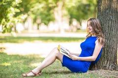 有美妙的浅褐色的头发的一个美丽的女孩在一棵大树附近坐并且读一本有趣的书在绿色公园 免版税库存图片
