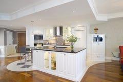 有美妙的海岛的现代开放白色厨房 免版税库存照片