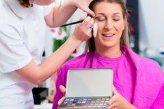 有美容师的妇女化妆沙龙的 免版税库存图片