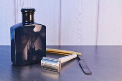 有美容水的老减速火箭的剃须刀在石桌上 库存照片