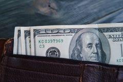 有美金的在木桌上,克洛老破旧的皮革钱包 免版税库存图片