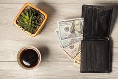 有美金的黑皮革钱包,咖啡和housep 免版税库存照片