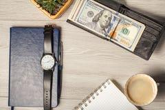 有美金的黑皮革钱包,笔记本, men& x27; s手表, p 免版税图库摄影