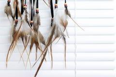 有羽毛螺纹的梦想俘获器和小珠系住垂悬,在背景的白色窗帘 手工制造的Dreamcatcher 免版税图库摄影