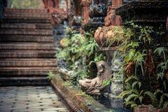 有老专栏的古老亚洲样式庭院胡同长满与热带植物和被弄脏的背景 免版税库存照片