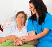 有老人的亲切的护士 免版税库存照片