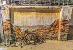 有老墙壁的老自行车 免版税库存照片
