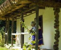 有老妇人的老木房子开花的种族礼服的 库存图片