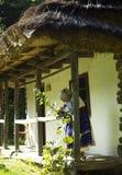 有老妇人的老木房子开花的种族礼服的 免版税库存照片