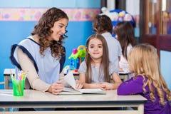 有老师和朋友的女孩在教室 库存图片