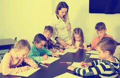 有老师图画的基本的年龄孩子在教室 免版税库存图片