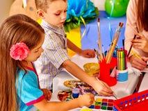有老师妇女绘画的孩子在纸 库存照片