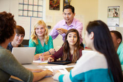 有老师的高中学生使用膝上型计算机的类的 库存图片