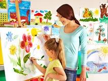 有老师绘画的孩子 免版税库存图片
