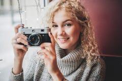 有老影片照相机的年轻白肤金发的卷曲女性在咖啡馆 免版税图库摄影